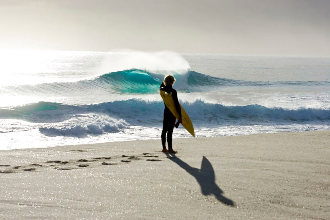 A surfer watching beautiful waves rolling in to the beach on King Island, Tasmania.